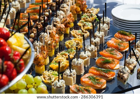 Catering service plate .appetizing sandwiches on plastic sticks rangeSandwiches on a table the buffet. meat, fish, vegetable canapes on a festive wedding table outdoor
