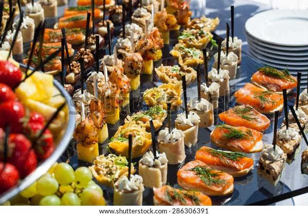 Plat de service de restauration .sandwichs appétissants sur bâtons en plastiqueSandwichs sur une table le buffet. viande, poisson, canapés de légumes sur une table de mariage festive en plein air