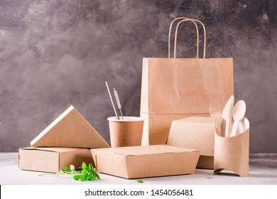 Catering and street fast food paper cups, plates and containers. Eco-friendly food packaging and cotton eco bags on gray background with copy space. Carering of nature and recycling concept.