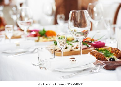 catering table set service with silverware, napkin and empty glass stemware at restaurant before party