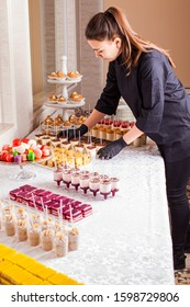 Catering waitress service. Woman at restaurant servicing dessert table