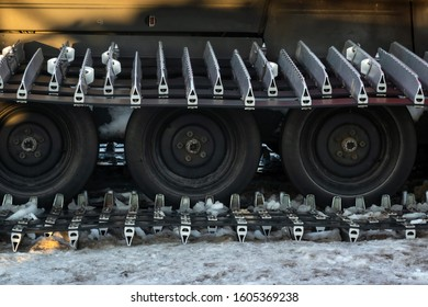 Caterpillar spikes on snowmobile in ski resort. Machine wheels with spikes for winter off road, extreme conditions. Tracked quad wheel, all terrain vehicle