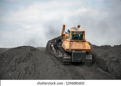 caterpillar tractor and travelling crane collect black coal to one big pile on supply field of thermoelectric power station