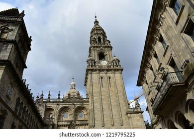 Cathedral. Baroque clock tower in romanesque facade with clean stone. Platerias, Santiago de Compostela, Spain. Atumn, cloudy grey sky.