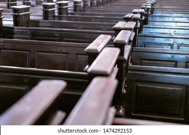 Cathedral benches. Rows of pews in christian church. Heavy solid uncomfortable wooden seats.