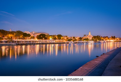 Cathedral, Giralda Tower and the Guadalquivir river in Sevilla, Spain. Blue hour view from Triana Quarter.