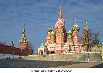 Cathedral of the Intercession of the virgin Mary, on the Moat (St. Basil's Cathedral) and the Spasskaya tower of the Moscow Kremlin on a Sunny winter day. Moscow, Russia