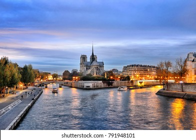 Cathedral Notre Dame along the banks of the river Seine, Paris, France seen from  pont de latournelle at twilight.
