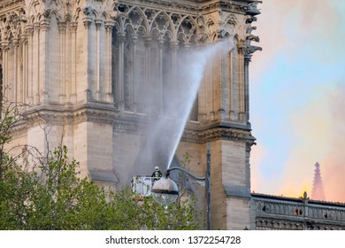 Cathedral Notre-Dame de Paris Fire, France 04/15/2019- Fireman trying to extinguish the fire with a water jet