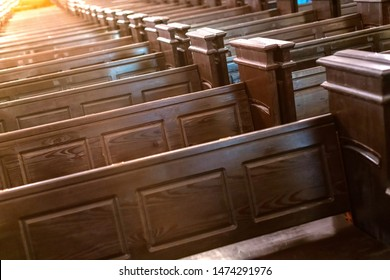 Cathedral pews. Rows of benches in christian church. Heavy solid uncomfortable wooden seats.