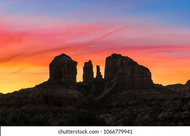 Cathedral Rock, a Sedona, Arizona iconic rock formation, is silhouetted by a dramatic and colorful sunrise sky.