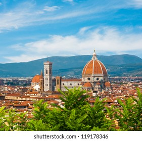 Cathedral Santa Maria del Fior, Duomo, with defocused green plants in front and beautiful sky in Florence, Tuscany, Italy