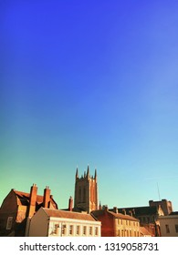 The cathedral tower and other buildings under a blue sky in Bury St Edmunds, UK