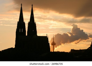 Cathedral with TV tower and smoke at sunset