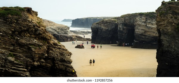 Cathedrals Beach's abrupt cliffs see people walking through them