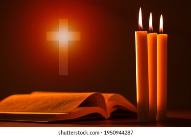 Catholic Bible next to candles. Burning candles near to bible. Religion Christianity. Concept - studying Christianity through Bible. Study of religion of Orthodoxy. Orthodoxy symbol near to candles