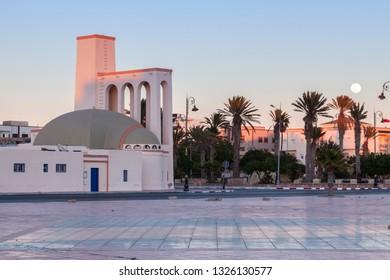 Catholic Church in Dakhla seen at sunset and moonrise. Dakhla, Western Sahara, Morocco.
