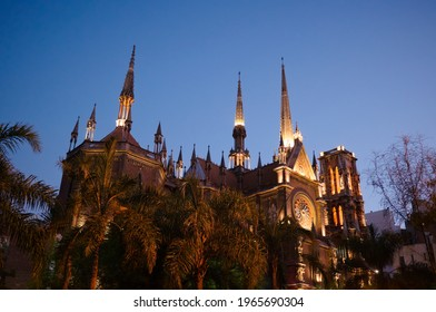 Catholic church in neo gothic architectural style with spires called Iglesia del Sagrado Corazon de Jesus also known as Iglesia de los Capuchinos. Gothic style illuminated church, palms in foreground