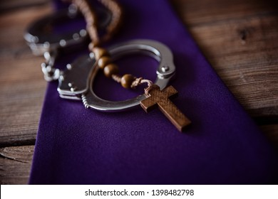 Catholic church symbols and handcuffs. Church and crime