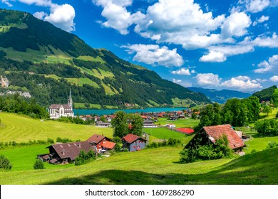 Catholic church, traditional wood and modern houses along the lake Lungernsee in swiss village Lungern in sunny summer day, Obwalden, Switzerland