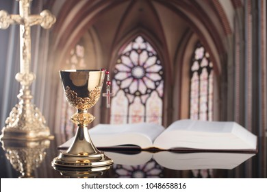 Catholic concept background. Golden chalices on the altar, bible, cross.