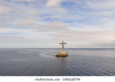 Catholic cross in a flooded cemetery in the sea near the island of Camiguin. Sunset over the sea. Cross on the flooded cemetery. Tourist place in the Philippines.