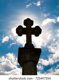 Catholic cross silhouette in backlight from the sun with blue sky and clud