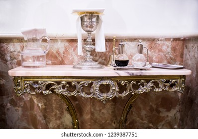 Catholic liturgical objects displayed over marble table at church. Chalice, wine and water pitcher, bell