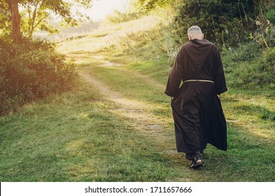 Catholic monk of the Capuchin Order, an adult wise man with a beard and in long dark brown clothing walks the stone path in the morning in nature