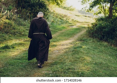 Catholic monk in robes praying in the woods. Copy space
