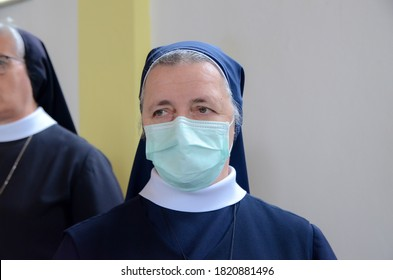 Catholic nun praying in church and wearing a face mask to protect herself from epidemic of coronavirus. Nun with medical mask in cathedral. Nun in religion black suit during the Mass. Covid-19