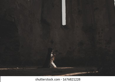 Catholic nun prays in the dark old church. Historical cosplay of vintage church. A woman in old nun catholic cassock
