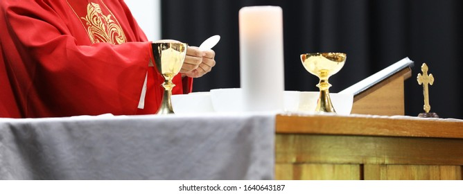 A Catholic Priest about to break the bread host while celebrating blessed Holy Communion at Mass. Wearing a red gown vestment and surrounded by chalice cross crucifix and bible