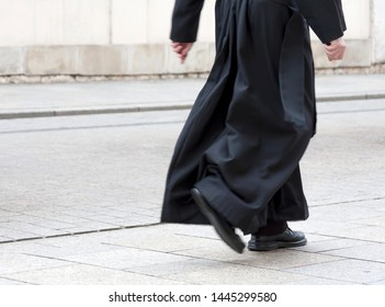 Catholic priest in the black cassock walking on the street solo, only legs visible. Clergy, faith, christianity and calling abstract concept