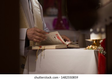 Catholic priest flipping through pages of the holy book on the altar during mass