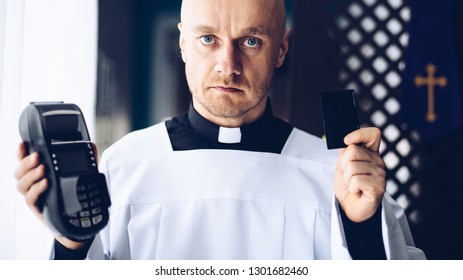 Catholic priest holding credit card reader. Money and religion