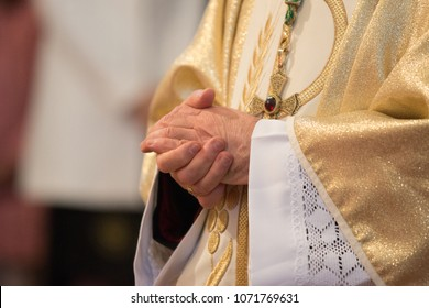 Catholic priest holding praying hands