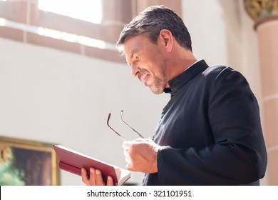 Catholic priest reading bible in church