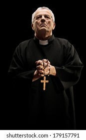 Catholic reverend holding a wooden cross isolated on black background