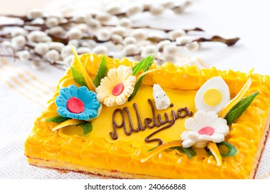 Catkins and yellow decorative Easter cake lying on material, Christians holiday symbol celebrating the resurrection of Jesus Christ, horizontal orientation, nobody in frame, objects in studio shot.