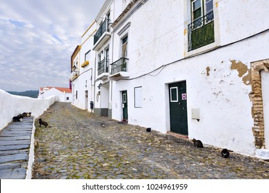 Cats on a typical narrow cobbled street in the ancient town of Mertola, Alentejo Region, Portugal.