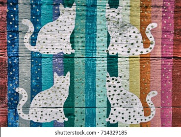 Cats in silhouette on multicolored striped wood panel background