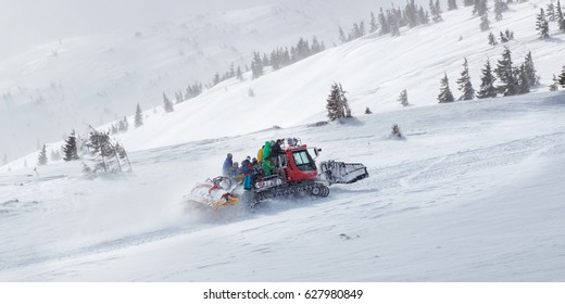Catskiing, cat, ratrack is unloading skiers for drop, skiing at the top of mountain. Freeride snowboards, Action and adventure for winter