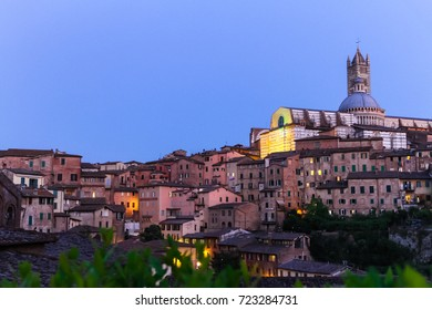 The Cattedrale metropolitana di Santa Maria Assunta or  Duomo di Siena shading by moonlight in August. Purple Sky and siena city in the scene.