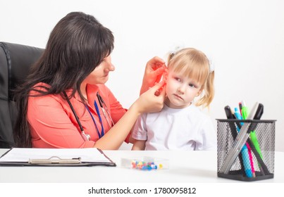 Cauacsian doctor otolaryngologist examines the ear of a little girl who has pain in her ear. The concept of otitis media and inflammation of the eardrum