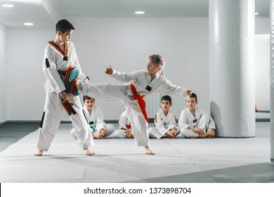 Caucasain boy and girl in doboks having taekwondo training at gym. Girl kicking while boy holding kick target. In background their friend sitting with legs crossed and watching them.