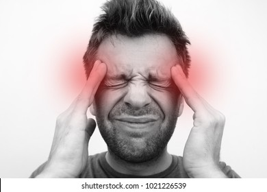 caucasain man with headache on white background close up. monochrome photo with red circle as a symbol of pain points