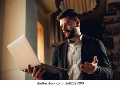 Caucasian adult bearded man indoors in cafe. Lifestyle concept photo with copy space. Picture with laptop, working near the window