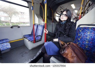 Caucasian adult woman in her early 30's sitting in a rather empty articulated bus, gazing into space waiting for her stop. Her clothing suggests it's winter time.