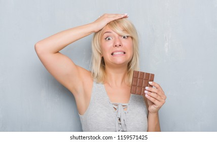 Caucasian adult woman over grey grunge wall eating chocolate bar stressed with hand on head, shocked with shame and surprise face, angry and frustrated. Fear and upset for mistake.